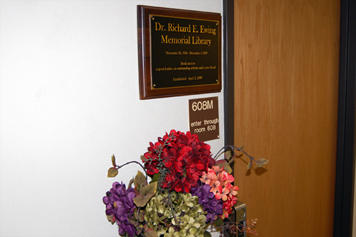 A photograph of the commemorative plaque and the door leading to the Dr. Richard E. Ewing Memorial Library.